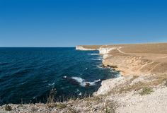 Steep cliff and azure water stock image