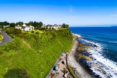 Steep cliff at Ballycastle, Northern Ireland, UK. Atlantic coast with a steep cliff, marina and Causeway Coastal Road at Ballycastle, County Antrim, Northern stock photography