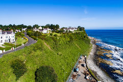 Steep cliff at Ballycastle, Northern Ireland, UK. Atlantic coast with a steep cliff, marina and Causeway Coastal Road at Ballycastle, County Antrim, Northern royalty free stock photos