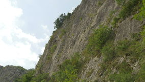 Steep Cliffs Wall. View of a high steep mountain slope with cloudy sky in the background, on summertime stock video