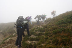Steep climb the mountain in fog. The rise of the mountain in fog Stock Images