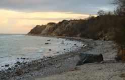 Steep coast with beach, stones and waves at the Baltic Sea in Mecklenburg-Western Pomerania, Germany, copy space. Steep coast with beach, stones and waves at the royalty free stock photo