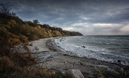 Steep coast with beach, stones and waves under a dark cloudy sky at the Baltic Sea in Mecklenburg-Western Pomerania, Germany, copy. Steep coast with beach royalty free stock images