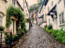 Steep cobbled street in Clovelly, Devon. The cobbled street in the quaint, picture postcard village of Clovelly, climbing up between the pretty houses on either stock images