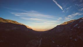 Steep dark mountainside with uplands beyond. Stock Photos
