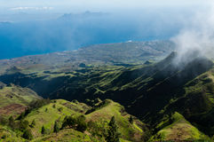 Steep green valley viewpoint leading to blue ocean Royalty Free Stock Photography