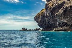 Steep high lava rock cliffs. Blue sea horizon, natural sky background stock photography