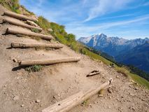 Steep mountain hiking trail with wooden steps royalty free stock photography