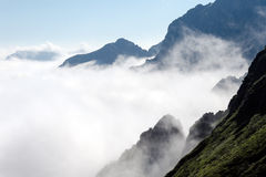 Steep mountain slopes and clouds. Steep mountain slopes and low clouds, temperature inversion effect, high mountain peak, above the clouds Stock Photos
