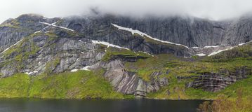 Steep mountains rising up from the Storvatnet near Nuffjord. Although it is mid june at sea level there are still patches of snow stock photo