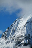 Steep mountainside with rocks, snow and ice stock images