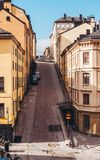 Steep and narrow cobblestone street with old buildings in Stockholm Sweden. Steep and narrow cobblestone street with two cars parked surrounded with old royalty free stock photo