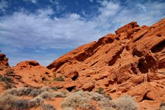 Steep orange rocks rising above the sandy floor and small scrub bushes in Nevada. A steep orange rock formation rises above the desert floor in Nevada, USA. The royalty free stock photography