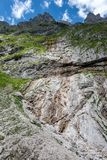 Steep rock face in the german alps. Steep rock face and a small waterfall in the german alps royalty free stock photography