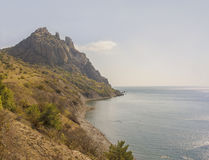 Steep rock shore and beach on the black sea coast.Crimea.  stock photos