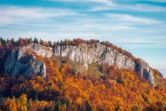 Steep rocky cliff above the forest in fall colors. Steep rocky cliff above the forest in reddish foliage. beautiful nature background stock image