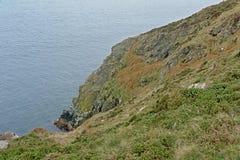 Rocky Cliffs along the north sea coast of howth , ireland. Steep rocky cliffs along the north sea coast of howth, ireland with on a cloudy day stock photo