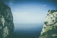 Steep rocky cliffs on coastline Stock Photography