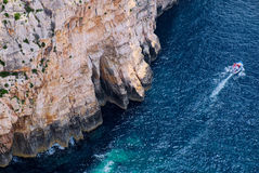 Steep sea cliffs and boat near blue grotto Royalty Free Stock Photography