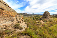 Steep sharp rocks surrounding a valley with trees and grassland Royalty Free Stock Photos