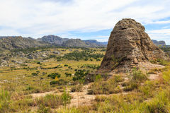 Steep sharp rocks surrounding a valley with trees and grassland Royalty Free Stock Image