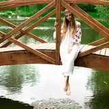 Steep slender Ukrainian woman resting sitting on a wooden decora. Beautiful slender Ukrainian in embroidery sits on the bridge over the water stock photography