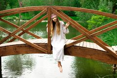 Steep slender Ukrainian woman resting sitting on a wooden decora. Beautiful slender Ukrainian in embroidery sits on the bridge over the water royalty free stock photos