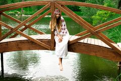 Steep slender Ukrainian woman resting sitting on a wooden decora. Beautiful slender Ukrainian in embroidery sits on the bridge over the water stock photos