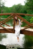 Steep slender Ukrainian woman resting sitting on a wooden decora. Beautiful slender Ukrainian in embroidery sits on the bridge over the water stock image