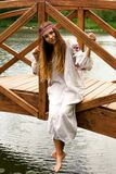 Steep slender Ukrainian woman resting sitting on a wooden decora. Beautiful slender Ukrainian in embroidery sits on the bridge over the water stock images