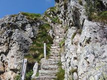 Steep stairway carved out of stone on a mountain path. Steel cables on its sides. Orobie. Italian Alps. Summer time royalty free stock photos