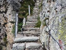 Steep stairway carved out of stone on a mountain path. Steel cables on its sides. Orobie. Italian Alps. Summer time stock image