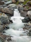 Steep stony stream bed of Alpine brook. Blurred waves of stream running over boulders and stones, high water level after rains. Steep stony stream bed of Alpine royalty free stock images