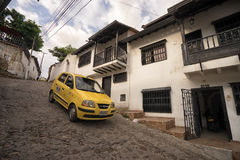 Steep street in Giron Colombia. July 23, 2017 Giron, Santander: a yellow small taxi descending a steep cobblestone colonial street Royalty Free Stock Image