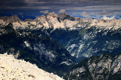 Steep Trenta Valley with Jalovec and Mangart peaks, Julian Alps. Dark green pine forests on ridges and steep slopes in Trenta Valley with Jalovec and Mangart Royalty Free Stock Images