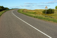 Steep turn ahead. Steep turn on country road and road sign Stock Photo