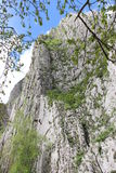 Steep vertical mountain rocks. Vertical steep mountain rock with rock climbers Royalty Free Stock Photo