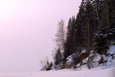 Shore of a frozen pond on the background of a setting frosty haze. Steep wooded shore of a frozen pond against the backdrop of a sunset frosty haze instead of Royalty Free Stock Photos