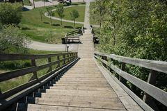 Steep Wooden Stairway Downward View. A steep wooden stairway with a downward perspective view. High height vantage into a park during a sunny day royalty free stock image