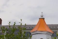 Steeple arancio d'imposizione interrompe Grey Sternness di questa scena del tetto e del cielo fotografie stock libere da diritti