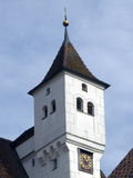 Steeple. Church tower of Ulm-Mähringen with tiled roof and clock Royalty Free Stock Image