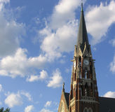 Steeple and Clouds. Very tall church steeple surrounded by blue sky and clouds stock image