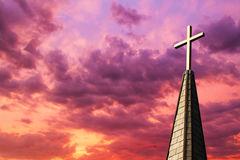 Steeple Cross at Sunset. Colorful sunset sky backs a gleaming golden cross high atop a church steeple stock image
