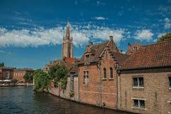Steeple e le vecchie costruzioni di mattone sul ` s del canale orlano in un giorno soleggiato a Bruges Fotografia Stock