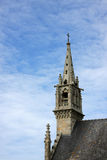 Steeple of a historic church. A steeple of a historic church with a crucifix on top photographed in the summer sun with blue and cloudy sky in the background Royalty Free Stock Photography