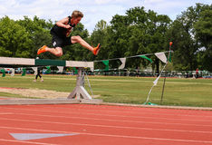 Steeplechase Athlete. A steeplechase participant clears his hurdle in good style  this event at this track meet in Redding, California April 26, 2014 Stock Image