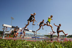 Steeplechase Track Men Jump Water. Competitors in the men's 3000-meter steeplechase at the Canadian Track & Field Championships June 28, 2014 in Moncton, Canada Stock Image