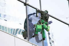 Steeplejack washes windows of a high-rise building Stock Images