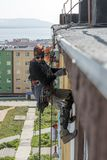 Steeplejack at work. On the wall of the building Stock Photography