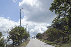 SteepTarmac Road with Heavy Cloudy Sky Royalty Free Stock Photography